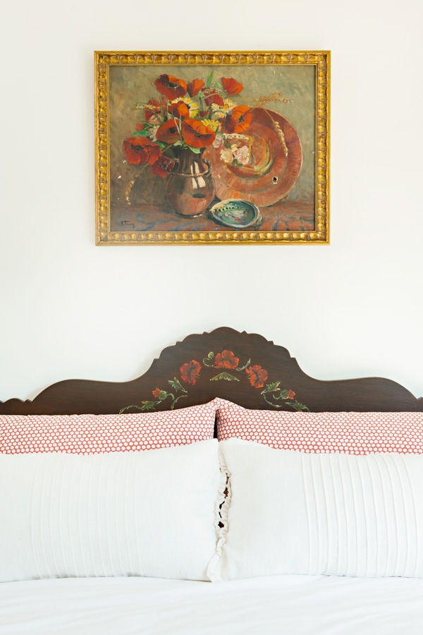 vintage paiting above an antique bed with painted detail and a gold frame.