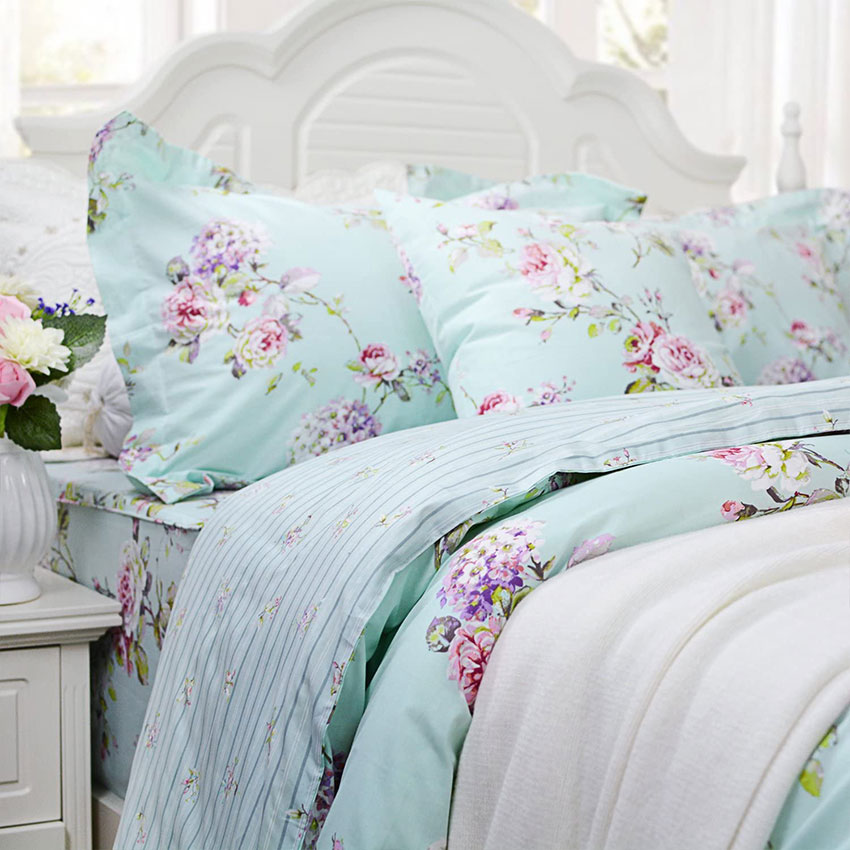 a baby blue and pink hydrangea duvet set on a white shabby cottage bed. Summer linen style.
