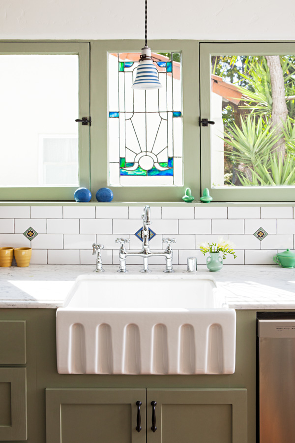 spanish bungalow kitchen after with stained glass and a farmhouse sink.