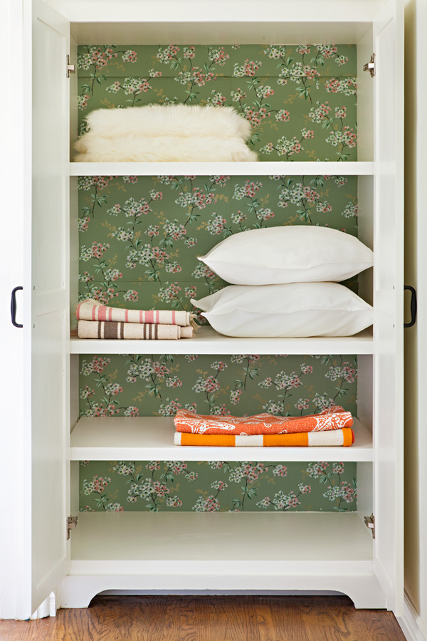 linen closet with vintage green floral wallpaper added to the back