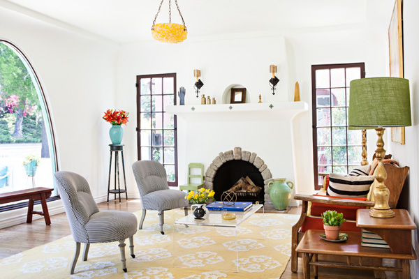 spanish bungalow living room with bright pops of color and a rounded fireplace opening.