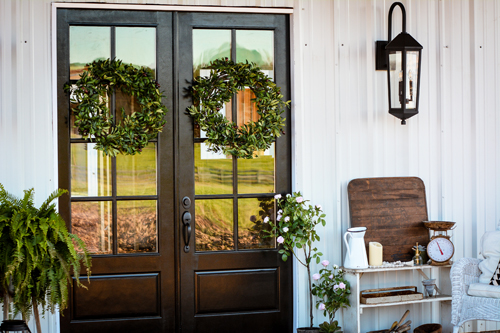 The front porch features elegant front doors that have been painted high-gloss black, which are complemented by the timeless lantern pendant by Capital Lighting. Lush wreaths from Balsam Hill warm up the entry with a dose of verdant green.