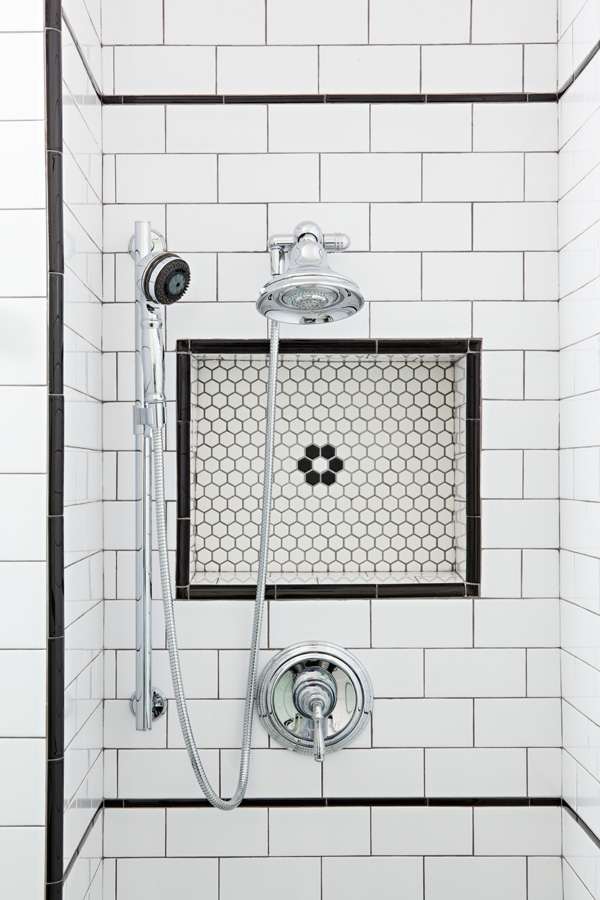 White hex tile with subway tile combo and black detailing in this renovated shower