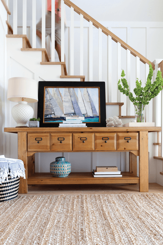 The light oak tones of the entryway carry the warm, welcoming feel of a farmhouse throughout the home. Keep the décor classic nods to the beach using coral, lush plants and a palette inspired by shades of the sea