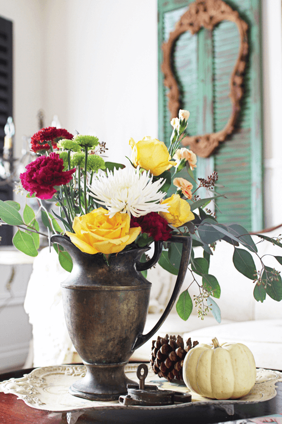 This vintage flower arrangement with a pumpkin accent make for a beautiful side table display.