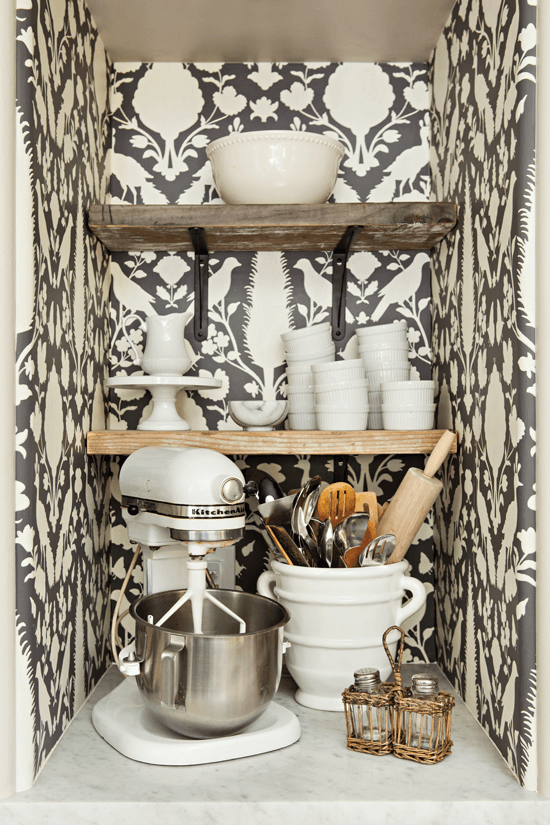 Melaine enlivened her kitchen-baking nook with Schumacher's Chenonceau wallpaper and created custom shelves for additional storage.
