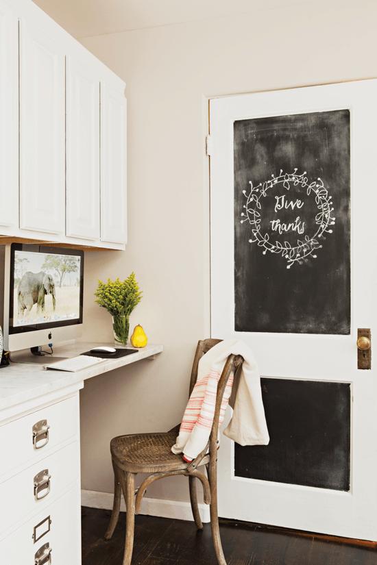 Corner desk with chair and chalkboard paint door.