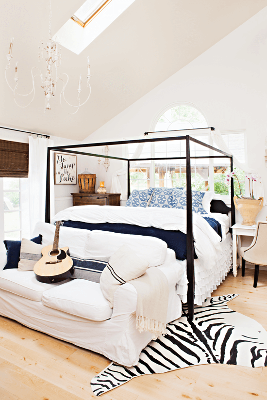 Airy master bedroom with high ceilings and hues of white, blue and black.