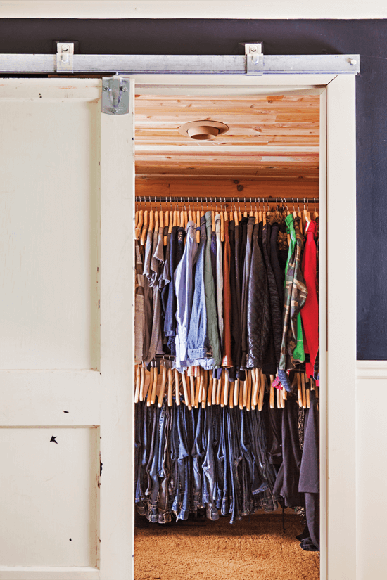 For a unique alternative to a standard sliding closet door, Melanie used an old barn door and hung it on a track. Inside the cedar-lined closet, metal pipe clothes rods give a rustic industrial sens