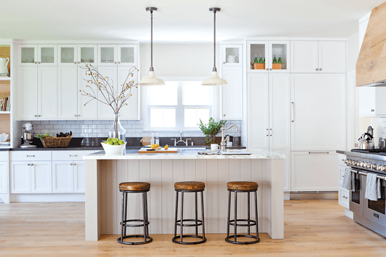 The distressed-oak range hood is a unique and rustic statement piece in this contemporary kitchen. Shabby yet chic barstools add rustic charm to the kitchen island.