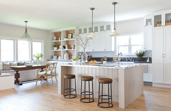 This sleek, contemporary kitchen features white cabinetry, high-end stainless steel appliances, a panel-covered refrigerator and freezer. A distressed oak range hood and accent kitchen island was added for a twist on the traditional look.