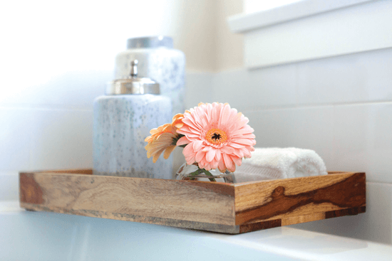 Utilize an old tray you have lying around in your home. Put together a few jars, some fresh flowers, and hand towels to create an inexpensive yet functional setup.