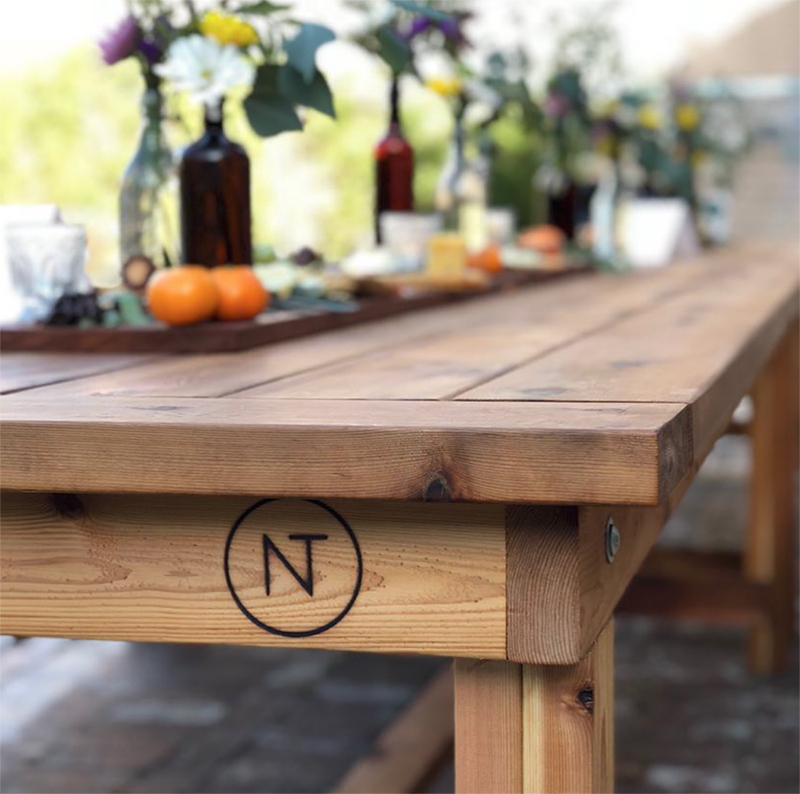 The classic wood table is a 9ft farmhouse-style table with wood benches and an authentic Neighbor's Table stamp. The tables' cedar material makes them perfect for outside use and allows them to last through years of meals and gatherings.
