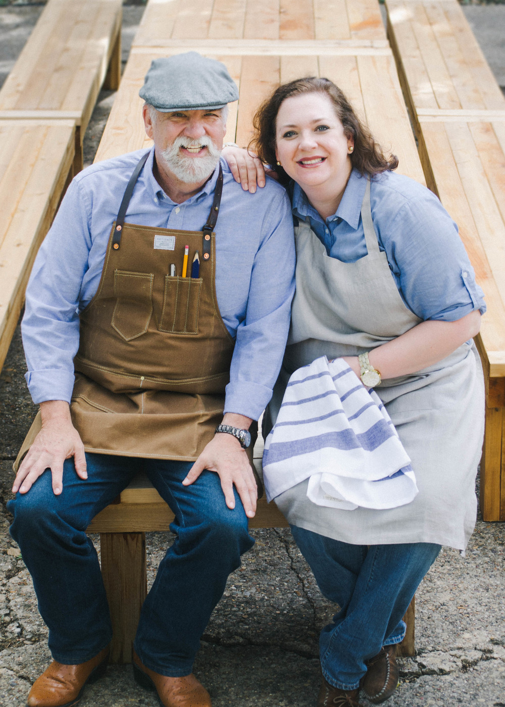 Sarah (right) pictured with her father, Lee (left), who is in charge of building the tables. He collects real cedar from a local lumbar yard and starts shaping tables that are customized by size and stain.
