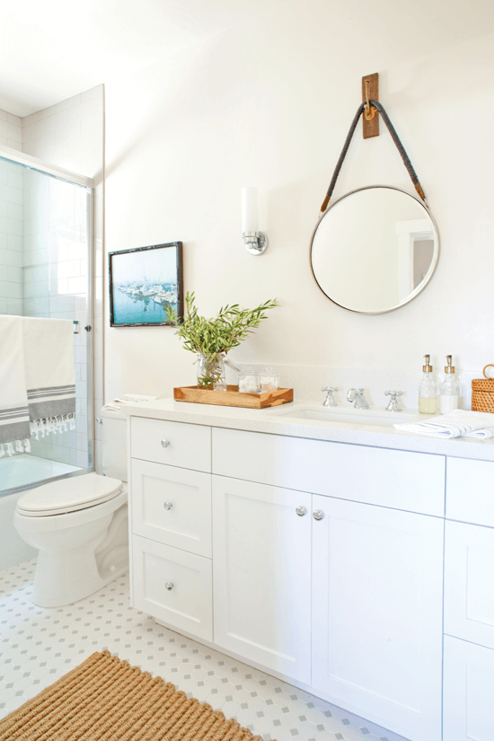The round mirror is reminiscent of a porthole—a sophisticated yet whimsical touch.
