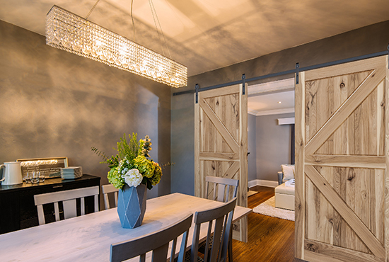 Woodgrain sliding barn doors, shown here in a dining room and living area.