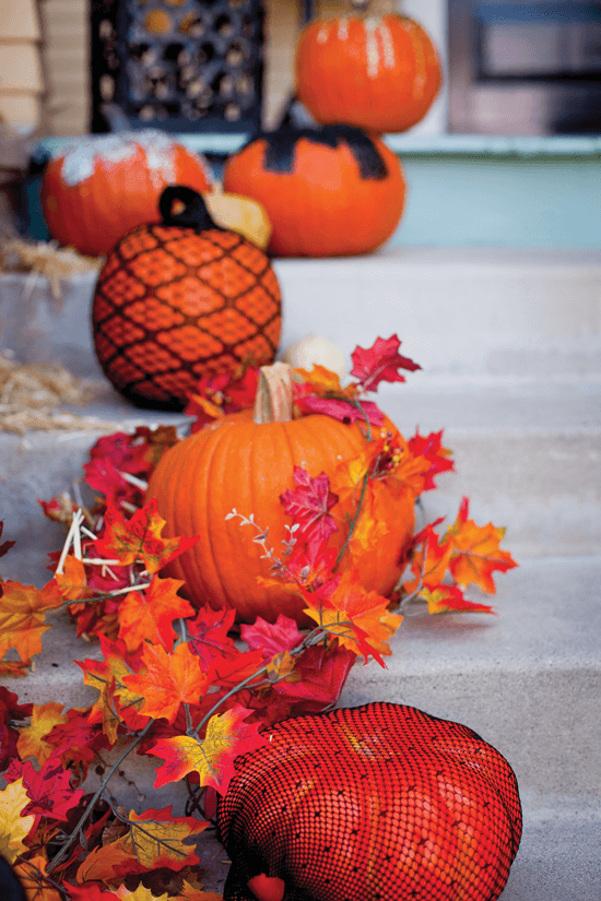 Draw the eye up to your door with a boost of curb appeal by lining your porch steps with a variety of pumpkins.