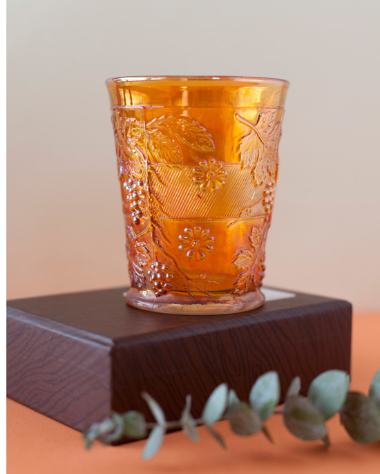 This carnival glass tumbler is by Indiana Glass and the pattern is called harvest grape in the amber marigold color.