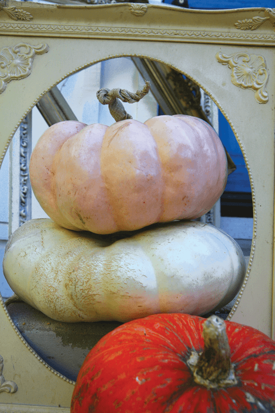 Use old frames and stacks of painted pumpkins to create unique and festive porch appeal for fall.