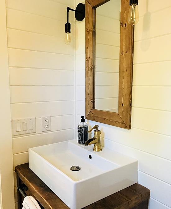 Bathroom vanity with wood-framed mirror and teardrop light fixtures.