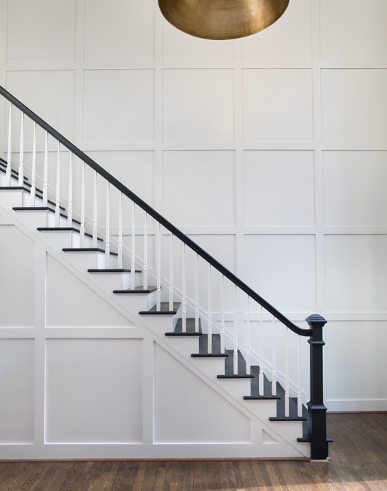 A staircase becomes a work of minimalist art, with the dark railing and steps contrasting against the white wainscoting.