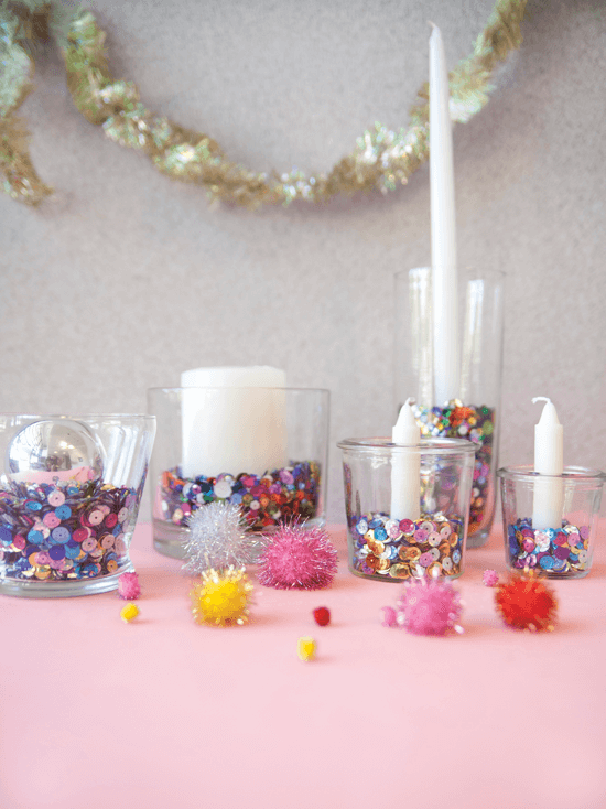 Sequin-filled glass tumblers topped with ornaments and candles.