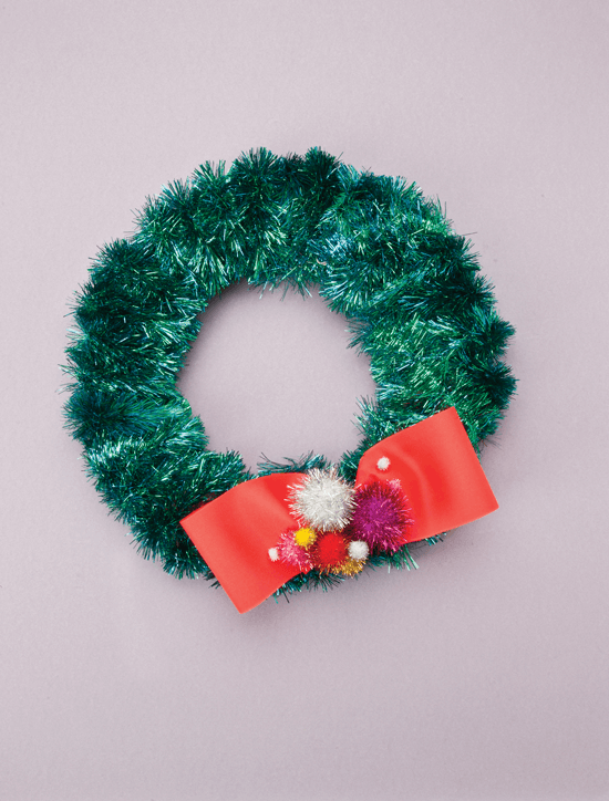 Holiday wreath wrapped in iridescent green garland finished off with a red bow and flashy pom-poms.