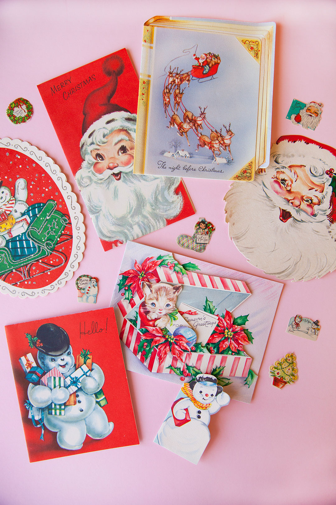 Vintage Christmas greeting cards on a pink background.