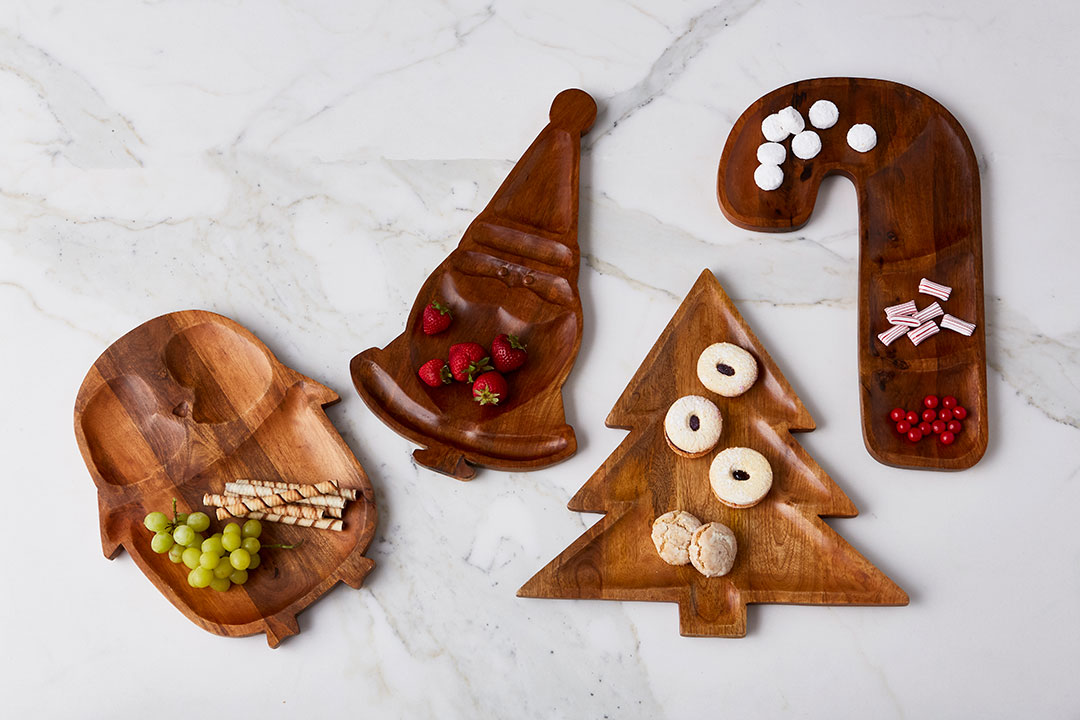 Carved mango wood platters featuring a penguin, Santa, a Christmas tree and a candy cane.