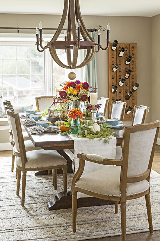 A colorful flower centerpiece sprinkled with greenery and a muted palette come together to create the perfect fall Thanksgiving table.