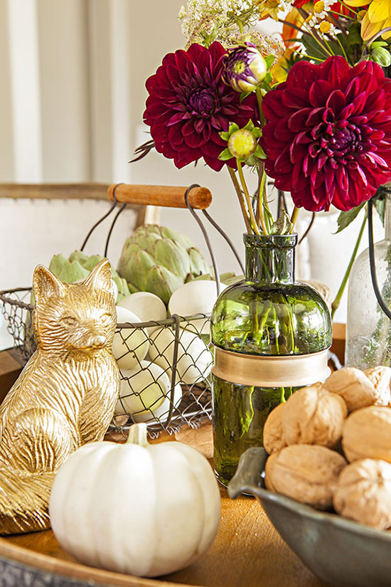 Centerpiece with bowl of walnuts, green vase of red dahlias, a golden fox and a white pumpkin.