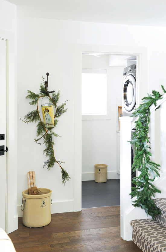 Light and bright home entryway decorated with greenery for the holiday season. // Cottages & Bungalows