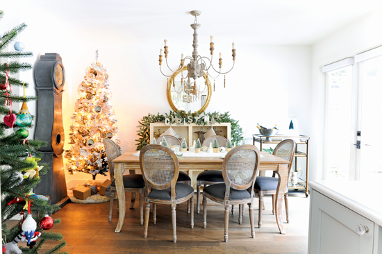 Dining room filled with French Christmas décor and a variety of textures, including greenery, rustic accents, a beaded chandelier and a patterned rug. // Cottages & Bungalows