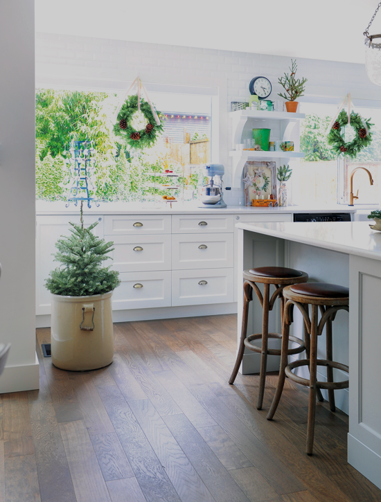 Various pieces of greenery are added to this white kitchen to complement the light foundation and give it a little bit of color. // Cottages & Bungalows