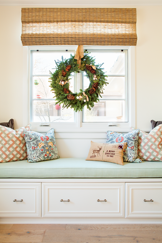 This custom-built window seat features a pinecone- and seashell-adorned wreath and mixed holiday pillows. // Cottages & Bungalows