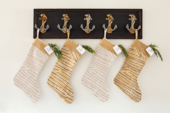 Instead of hanging above the fireplace, these stockings are hung beautifully from a piece of wall art with anchor hooks.