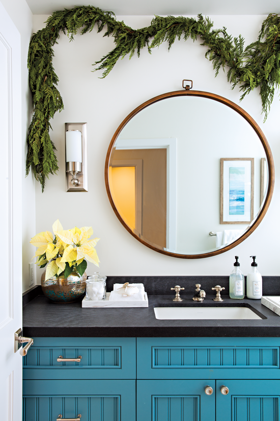 The space behind this coastal blue bathroom vanity is full of Christmas cheer with the addition of green garland.