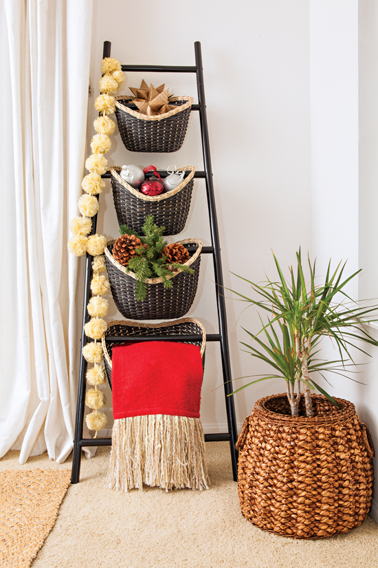 With a dash of creativity, a small black ladder is used as a place to spotlight baskets, a throw, decorations and a garland.