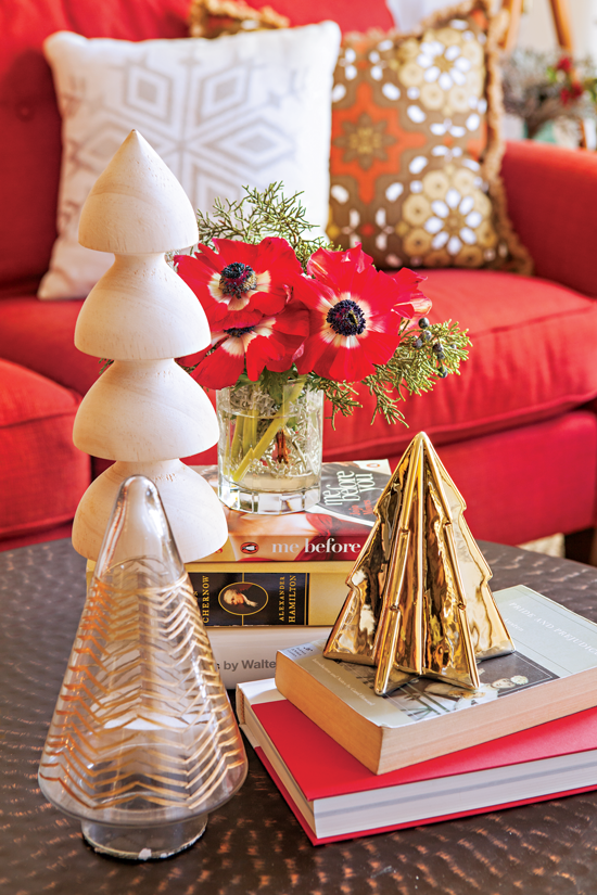 This stack of books serves as a landing pace for holiday décor, including small trees in a variety of materials and a vase of bright red anemones.