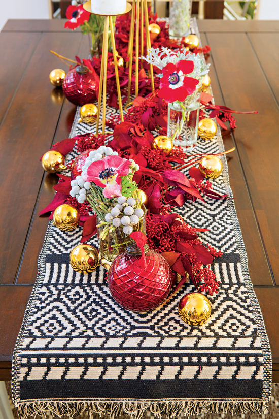 A tribal textile brings in the bohemian edge while red dyed eucalyptus and red cosmos add an artsy element.