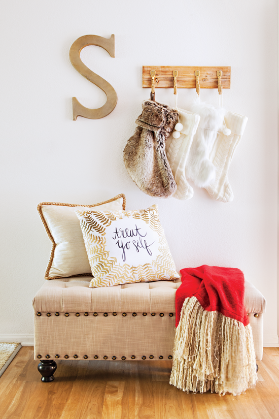 An entryway featuring an ottoman and throw pillows is transformed into a place to welcome Christmas guests. The scene is set with a red blanket and oh-so-fuzzy stockings.