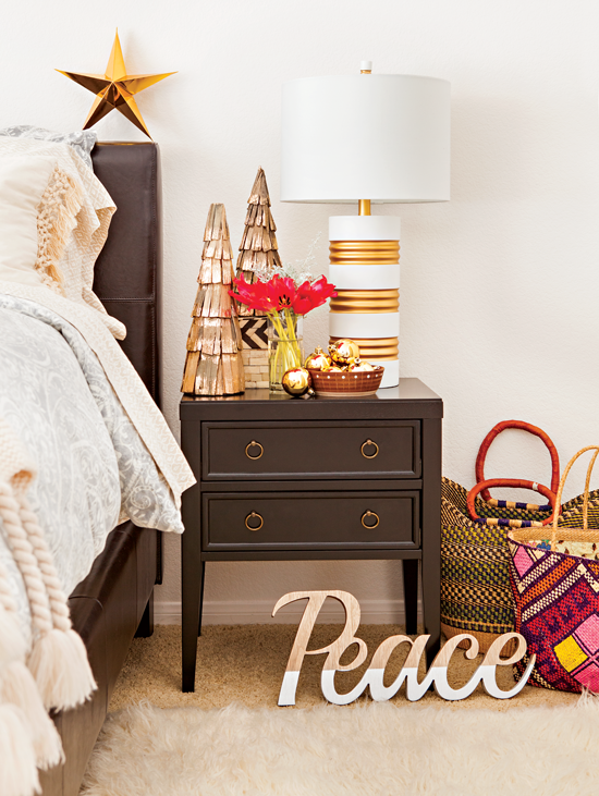 Bedroom size table decorated with simple Christmas tree figures, red flowers and gold ornaments.