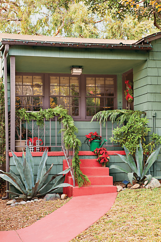 Front porch of home with a dark green exterior and red accents on the stairs and trim.