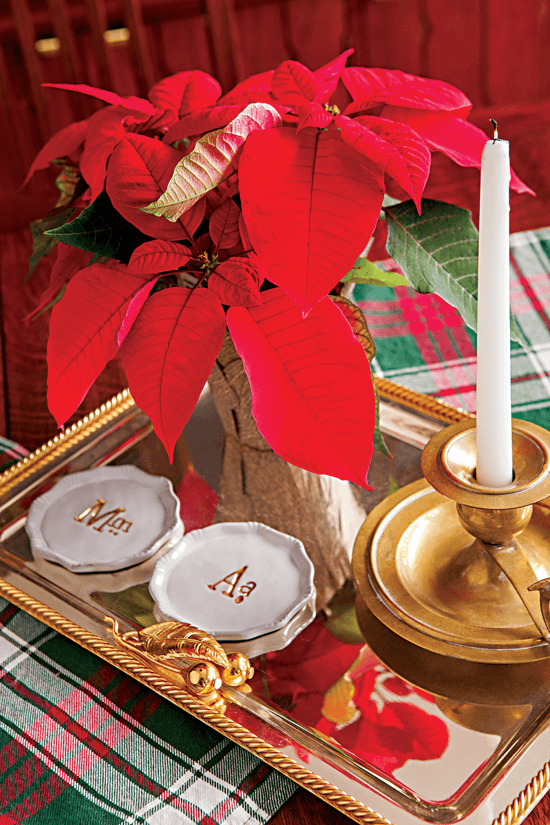 Tabletop display featuring a poinsettia, white monogramed plates and a candlestick arranged on a gold tray.