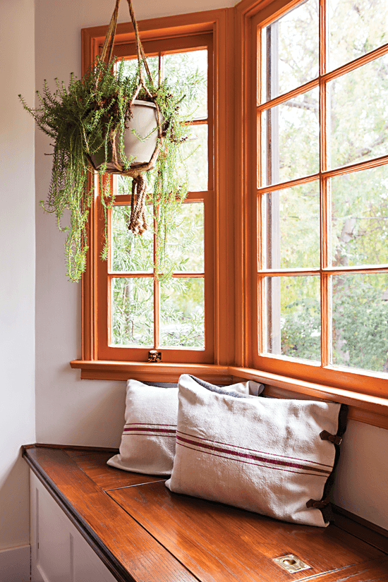 Handcrafted oak window seat and storage bench combo, styled with throw pillows made from Hungarian grain sacks.