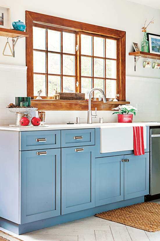 The large window over the kitchen sinks lets in a lot of natural light and enhances the beauty of the blue lower cabinets.
