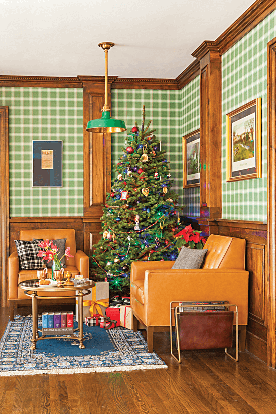Cozy lounge area with adorned with British pub-inspired hues and a Christmas tree in the corner. Two tan armchairs are positioned on either side of the Christmas tree.
