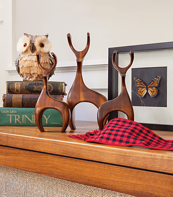 Wooden deer figures sitting on the media cabinet in the living room just below the television.