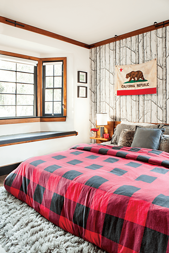 A cozy red-and-black plaid blanket is a seasonal addition to the bed, while the birch tree wallpaper and soft gray rug evokes snow.