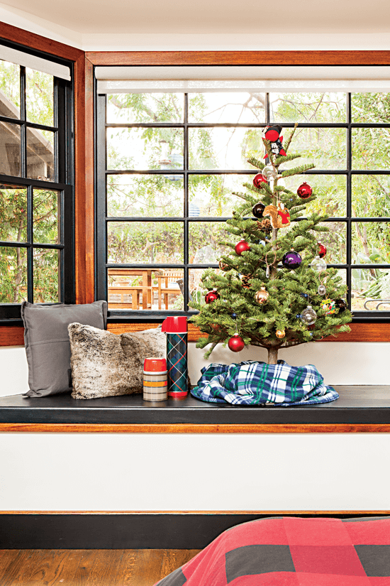 Stained mahogany trim around the window seat gives the bedroom a timeless look, while the decorative elements—a mini Christmas tree paired with a fur pillow and plaid thermos—tie in with the room's outdoorsy, wintry style.